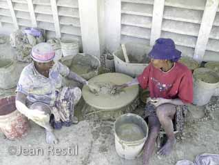Two Haitian women sifting the clay for té